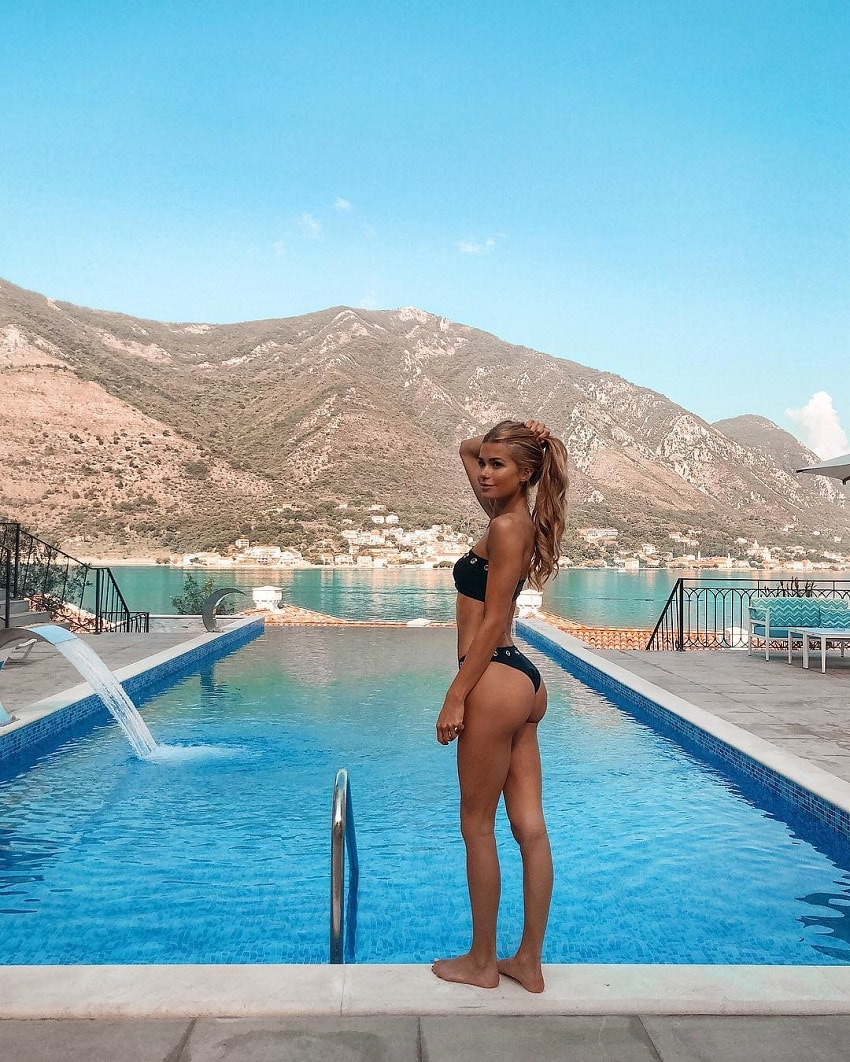 Pamela Reif showcasing her glutes by the pool with a beautiful mountain in the background