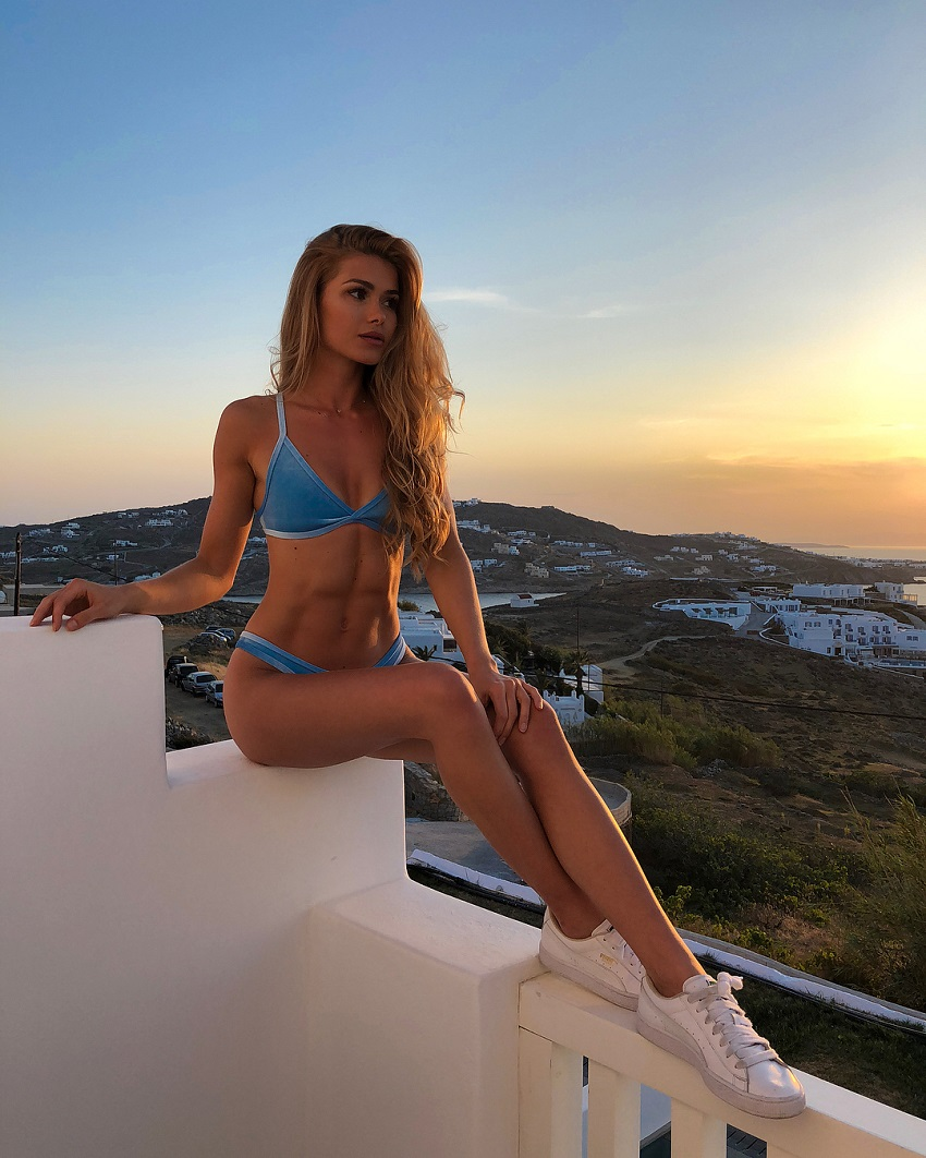 Pamela Reif sitting on a balcony with a beautiful view looking fit and lean