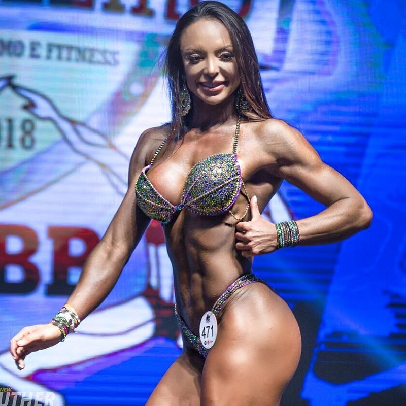 Pri Santtana showing off her sculpted figure in front of judges on a bodybuilding stages