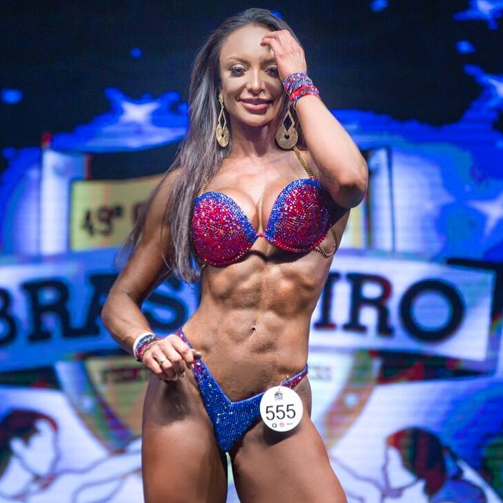 Pri Santtana posing and smiling on a bodybuilding stage