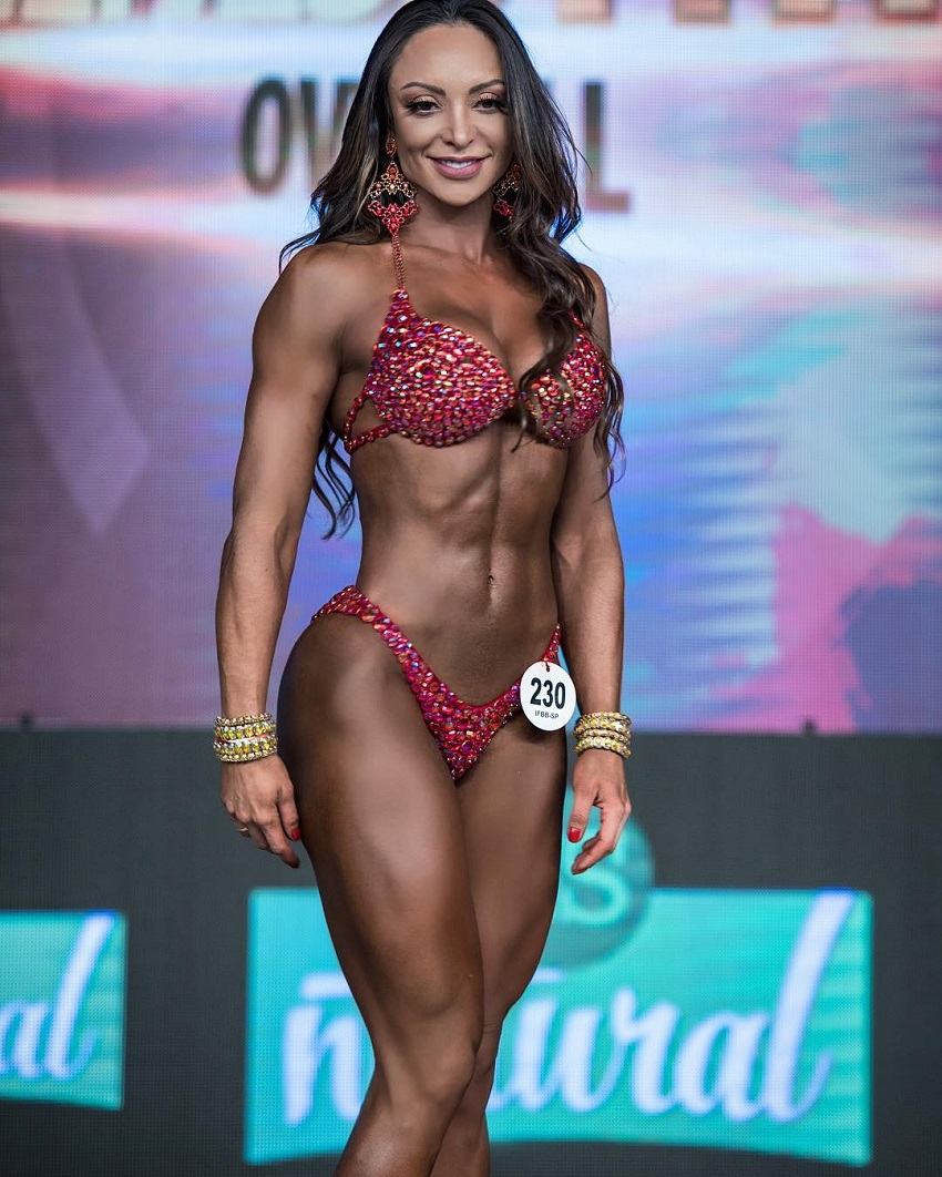 Pri Santtana standing on a bodybuilding stage smiling at the judges