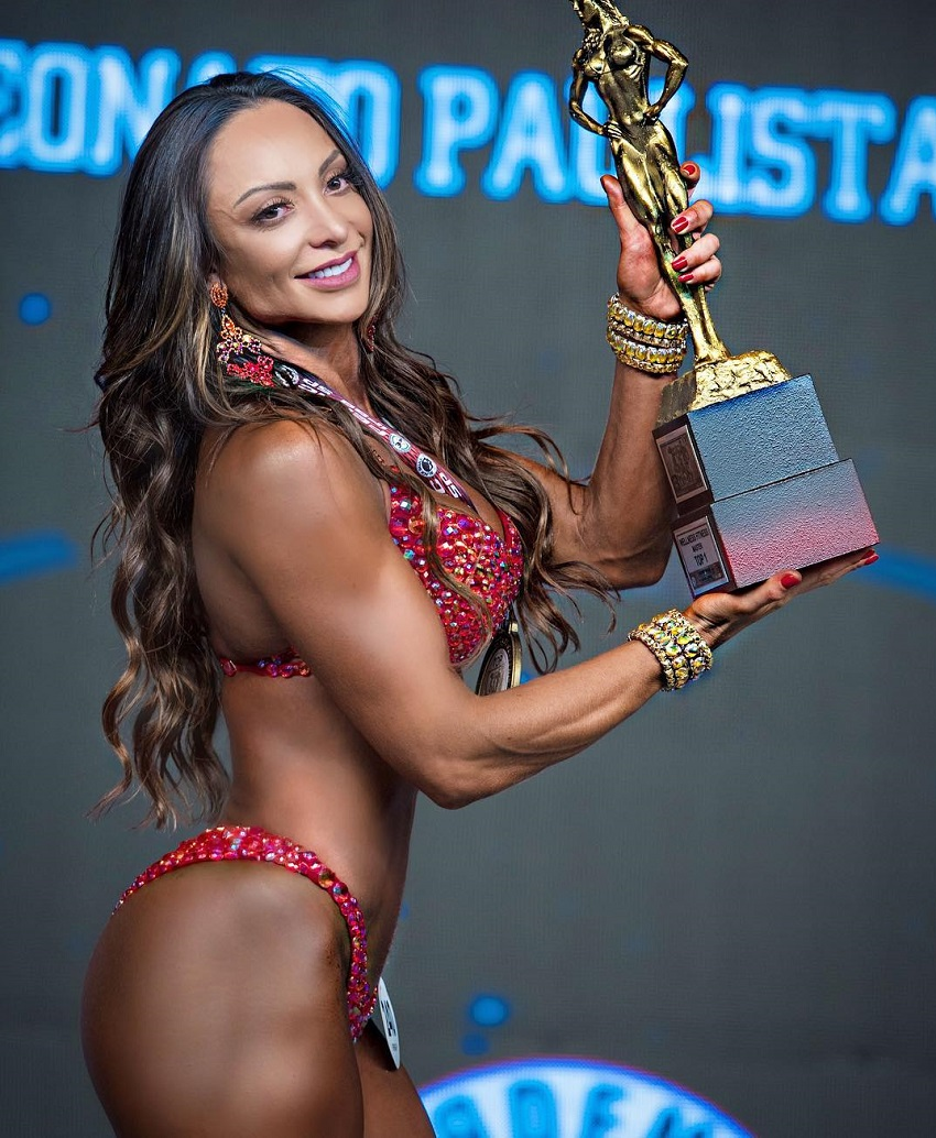 Pri Santtana posing on the fitness stage with a trophy in her hands