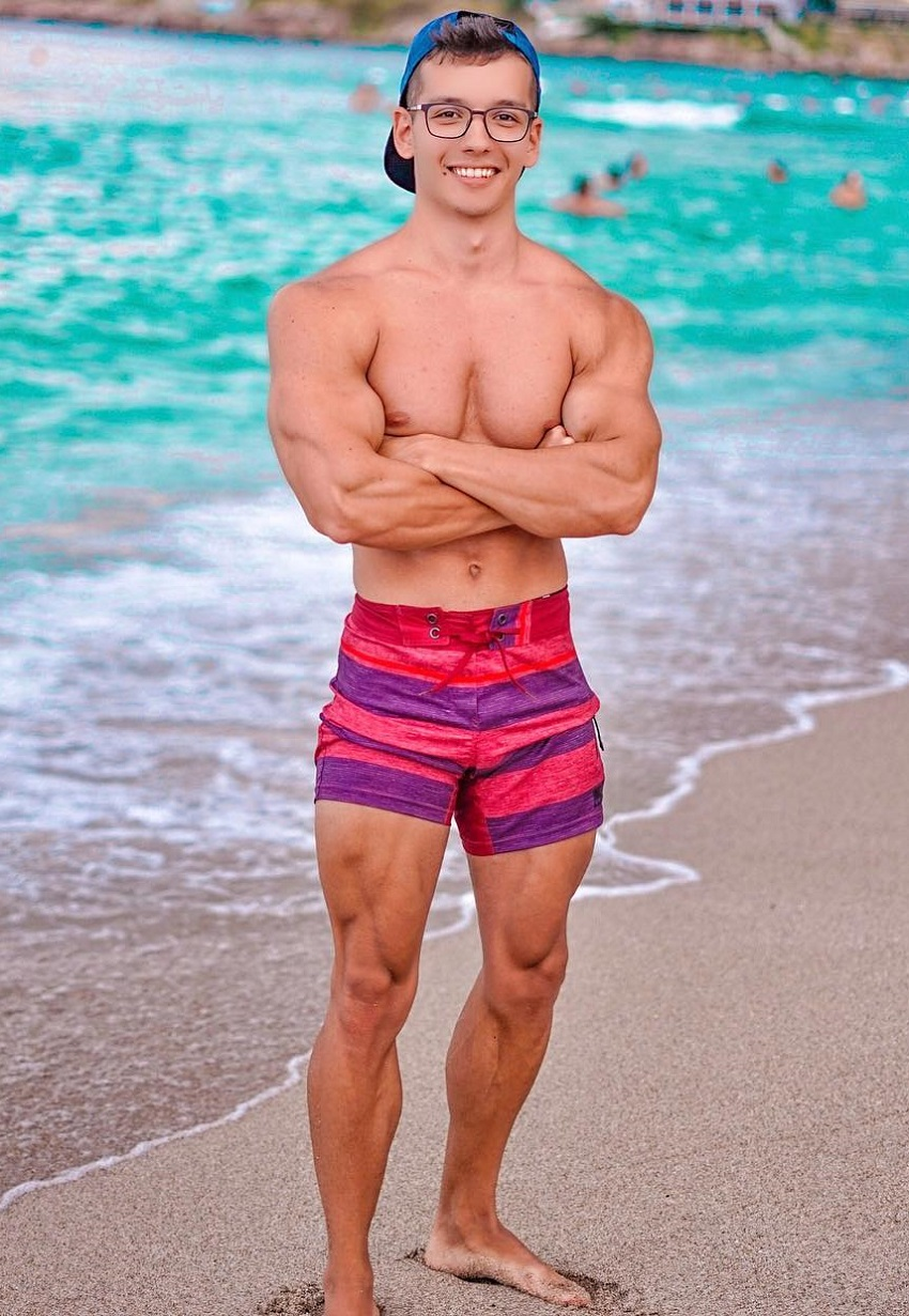 Radoslav Raychev standing shirtless on the beach looking strong and ripped
