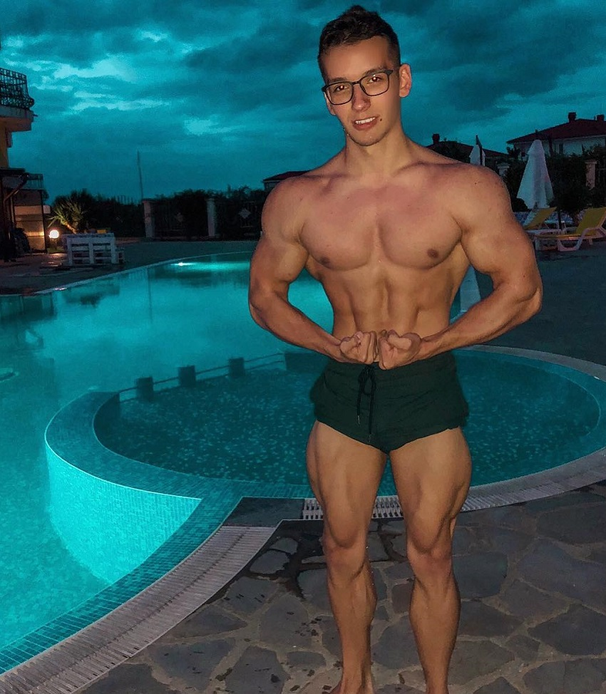 Radoslav Raychev flexing his muscles for a picture standing in front of a pool