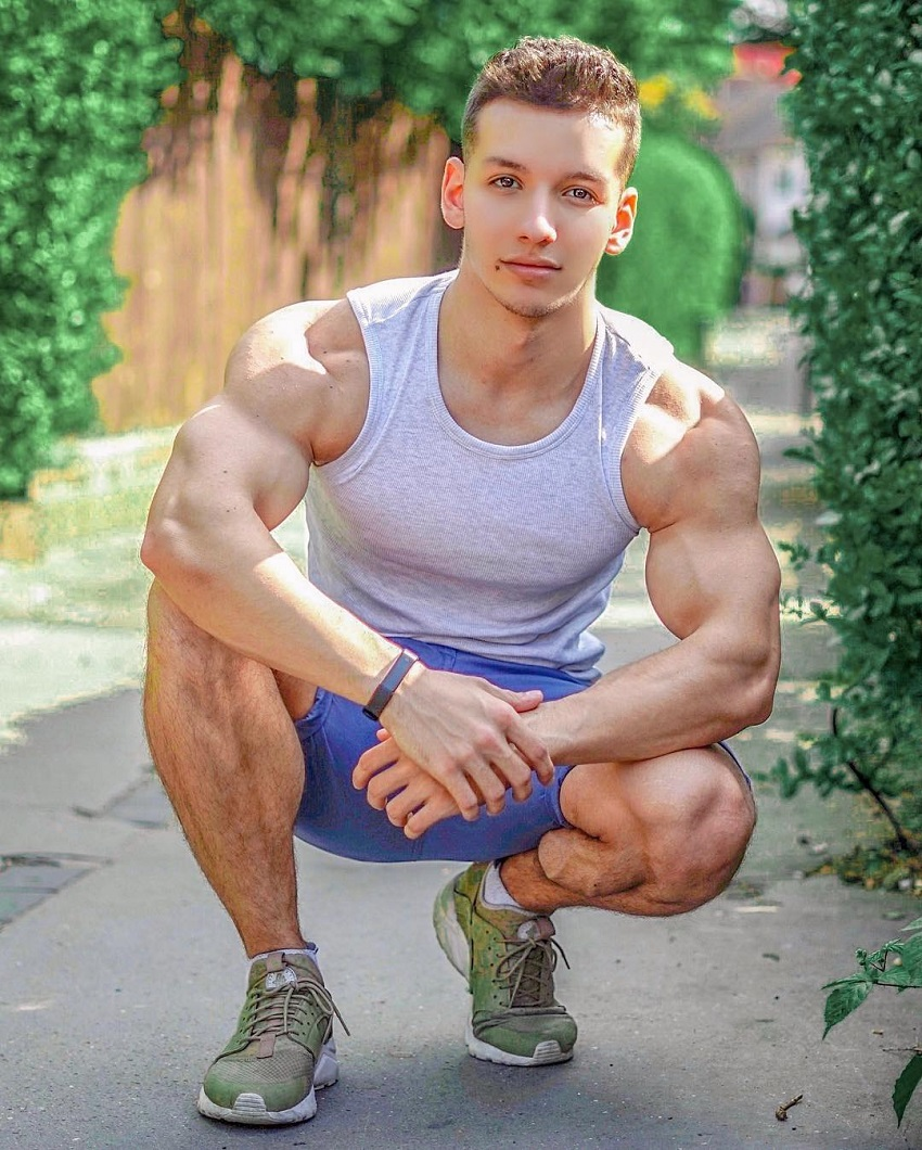 Radoslav Raychev crouching, showing off his remarkable physique in a grey tank top