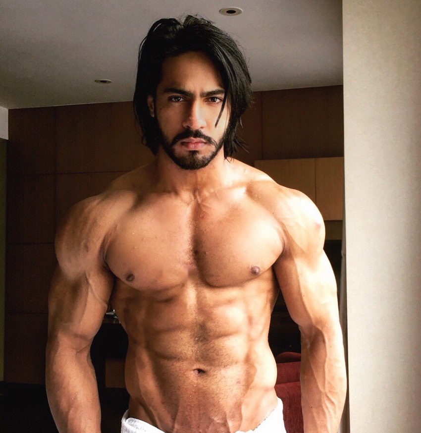 Thakur Anoop Singh posing shirtless with a towel around his belt looking strong and ripped