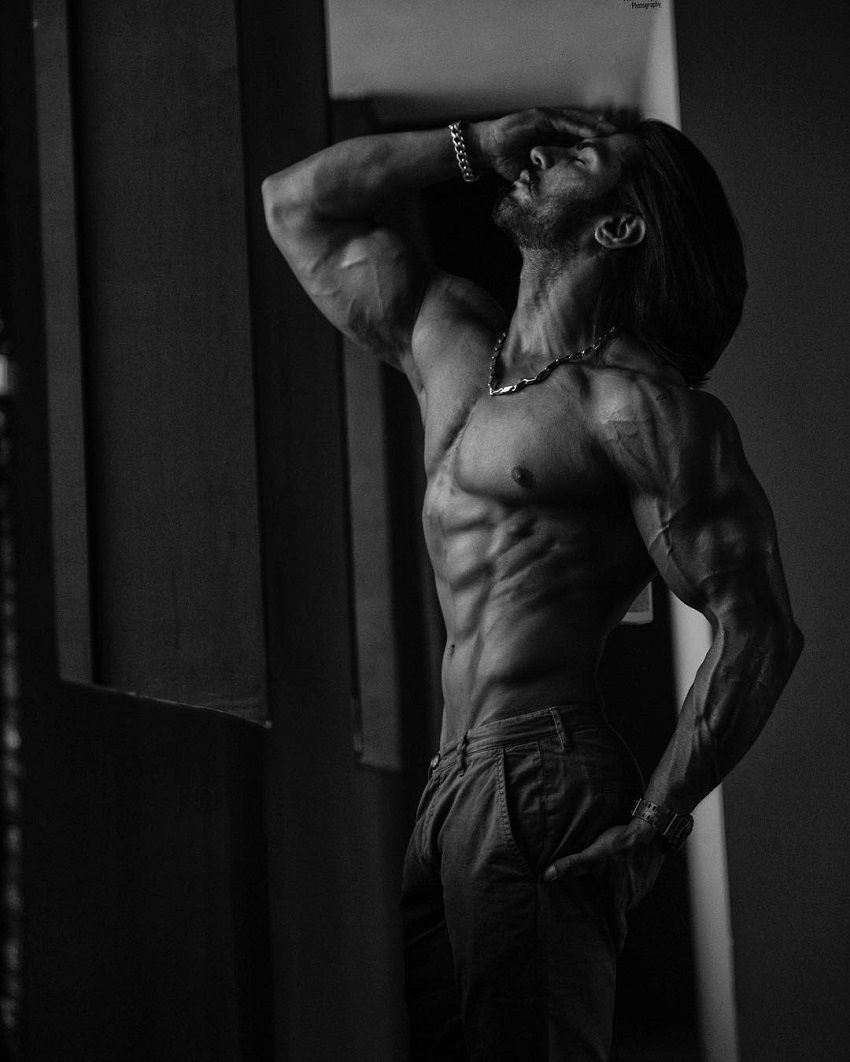 Thakur Anoop Singh posing shirtless in a white and black photo looking ripped
