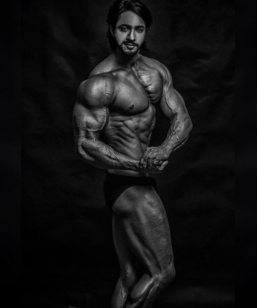 Thakur Anoop Singh flexing for the photo looking ripped and muscular
