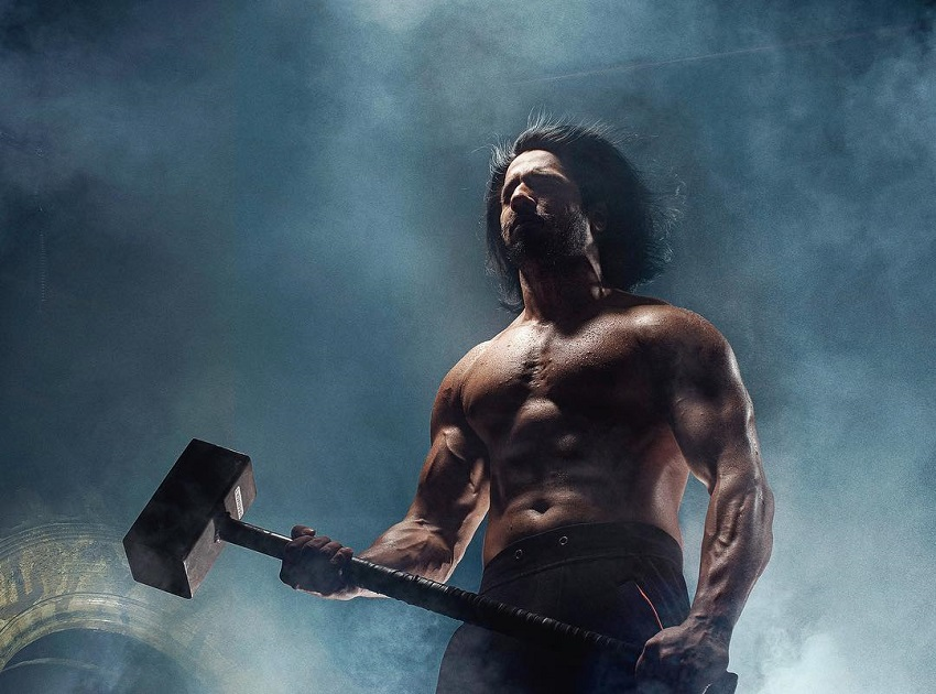 Thakur Anoop Singh posing with a sledgehammer in his hands looking strong and fit