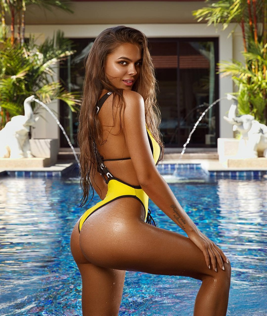 Viki Odintcova posing next to a pool showcasing her awesome glutes