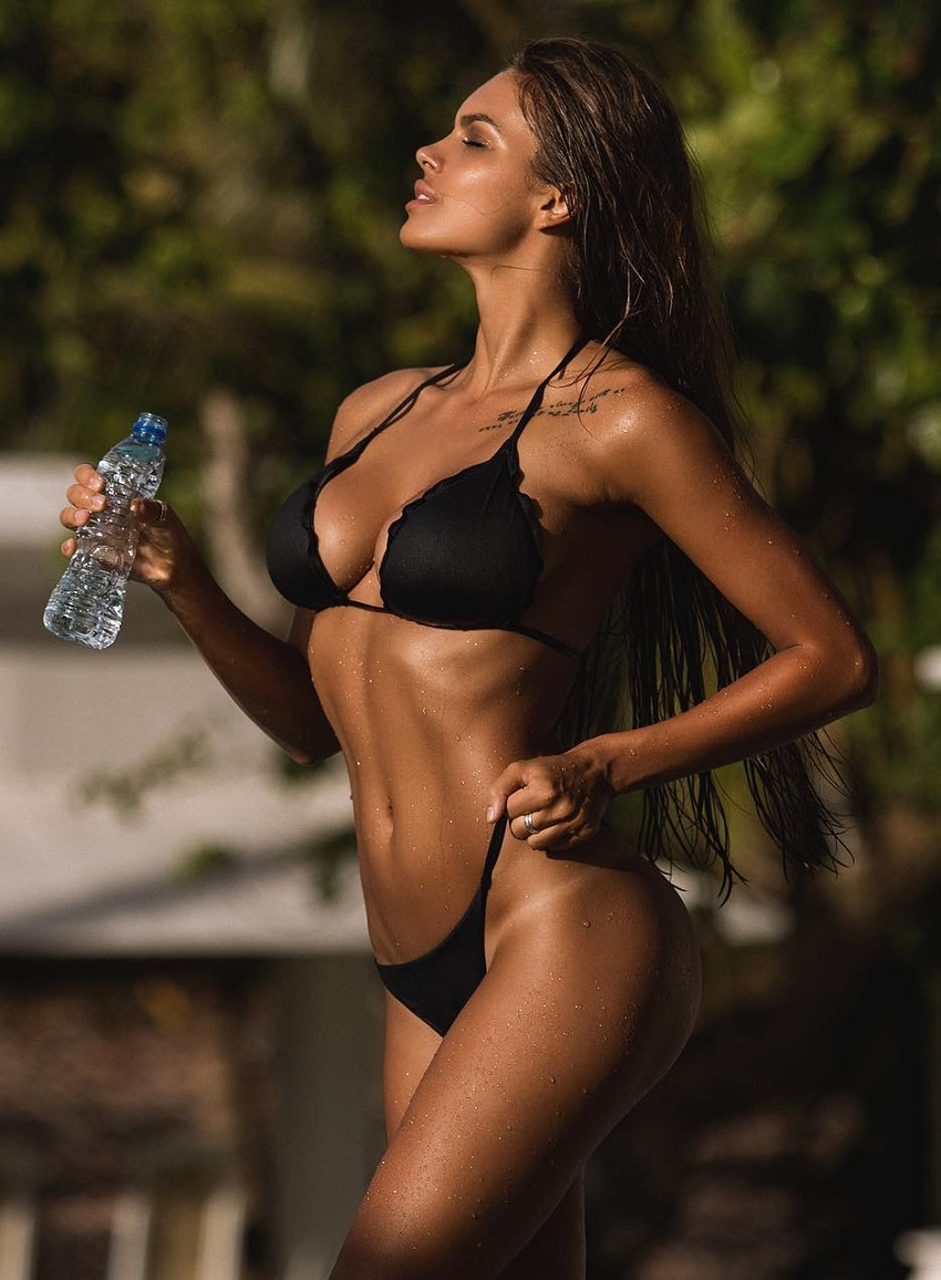 Viki Odintcova posing in a black bikini looking fit and lean