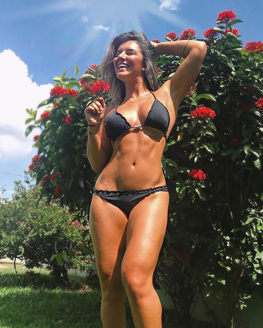 Vitoria Gomes smiling and posing in a bikini with her lean abs