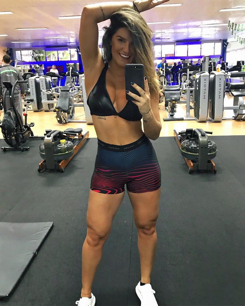 Vitoria Gomes taking a selfie of her aesthetic figure in the gym