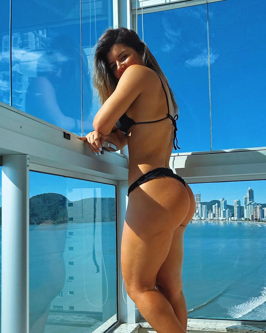 Vitoria Gomes posing on a balcony showing off her curvy and toned legs