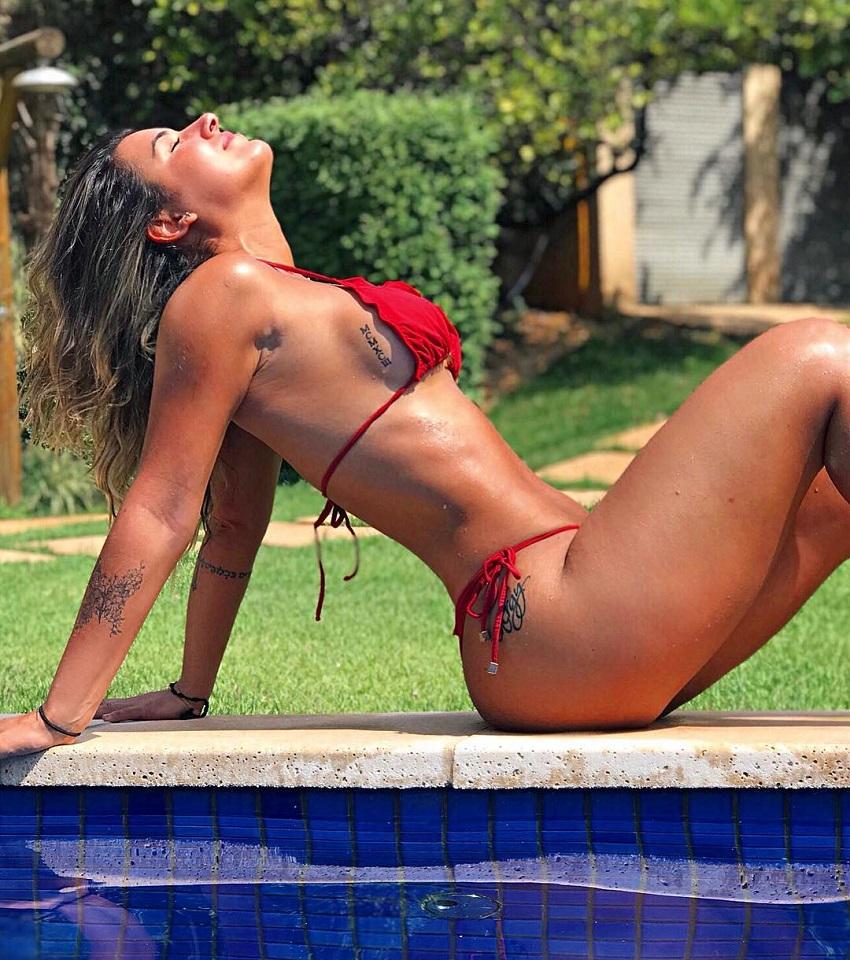 Vitoria Gomes posing by the pool in her red bikini