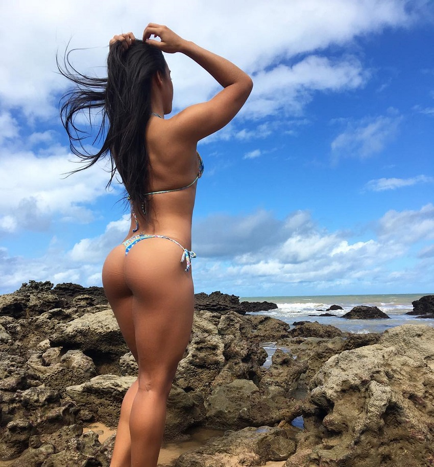 Amanda Choairy standing on a rocky beach showcasing her curvy legs and glutes