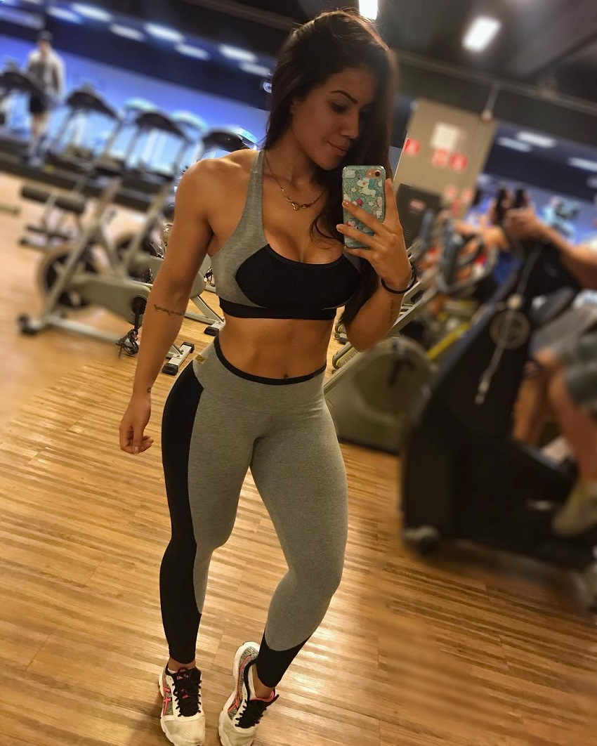 Andressa Gil taking a picture of her lean and fit physique in a gym