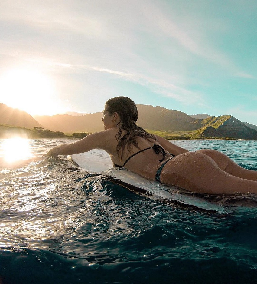 Angelica Kathleen lying on a surfboard in sea in Hawaii