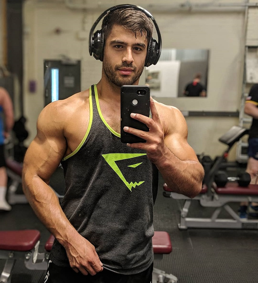 Dan Tai taking a selfie of his muscular physique in a tank top