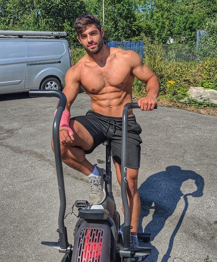 Dan Tai sitting shirtless on a cardio bike machine outdoors