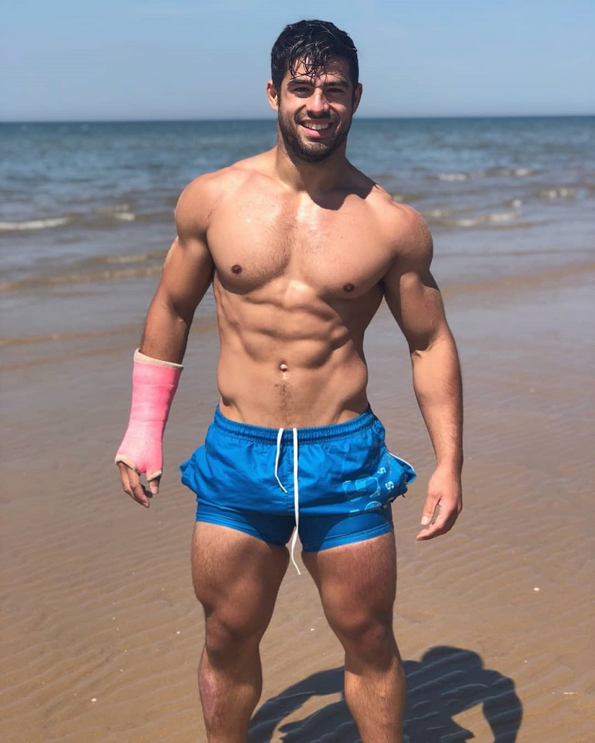 Dan Tai posing shirtless on the beach looking fit and lean