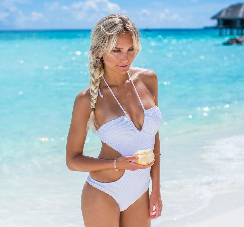 Faya Nilsson enjoying the sunny weather outdoors by a beach in her exotic white swimsuit