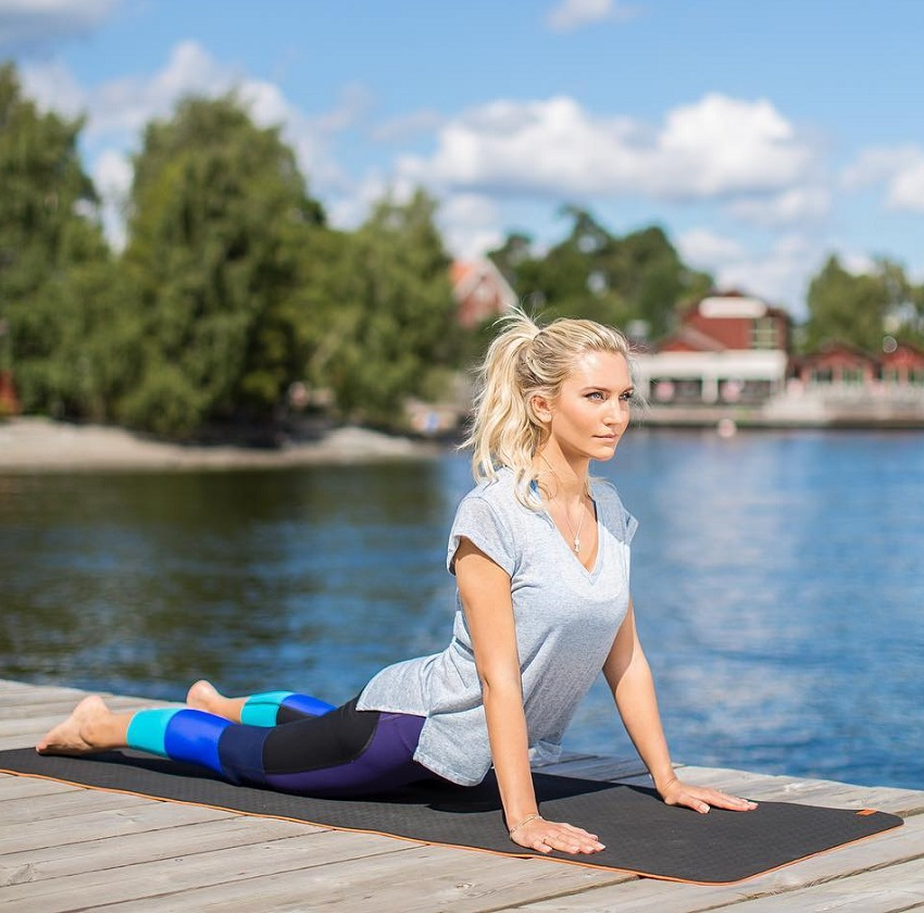 Faya Nilsson stretching outdoors on a yoga mat near a lake, looking fit and lean