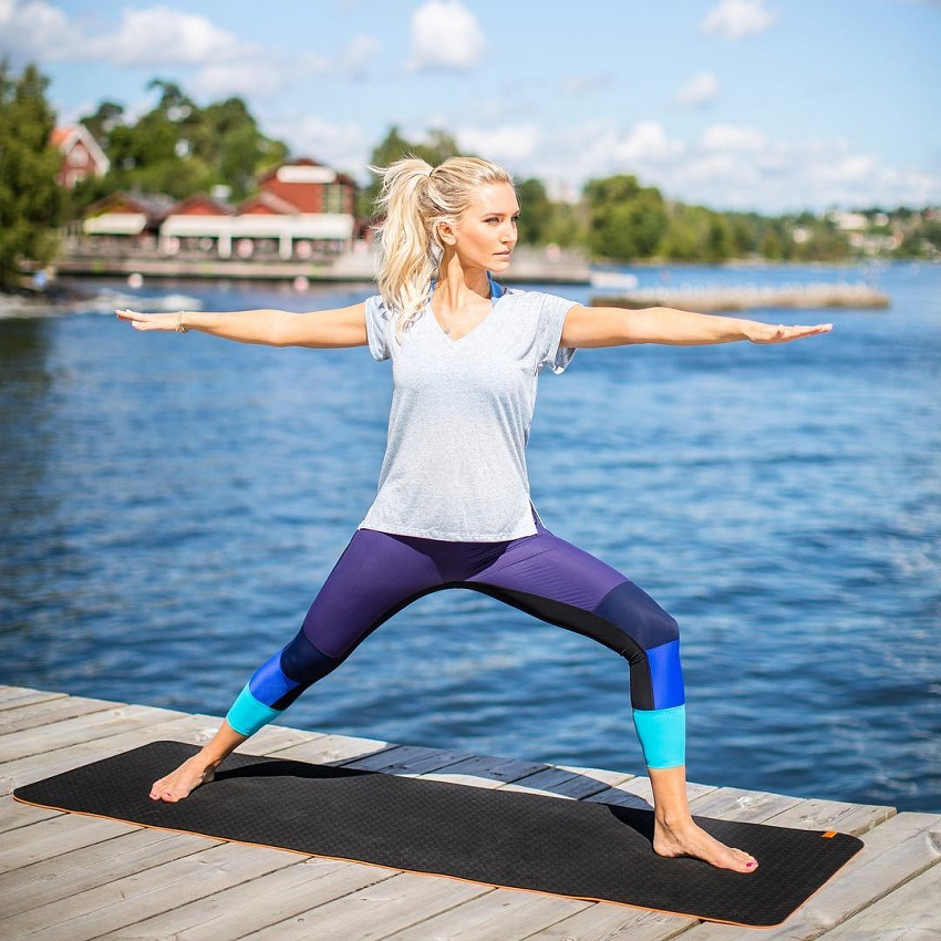 Faya Nilsson performing yoga by a lake