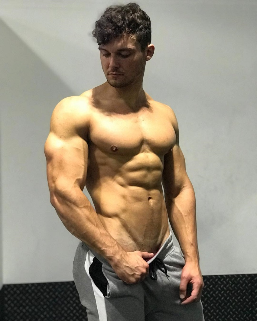Josh Watson posing shirtless for a photo looking muscular and ripped