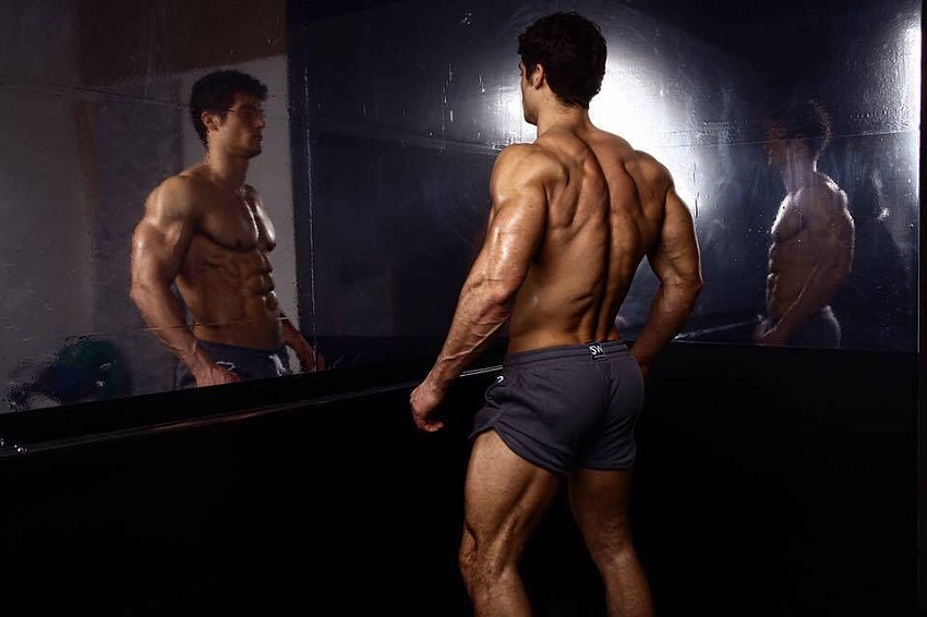 Josh Watson looking at himself in the mirror looking strong and lean
