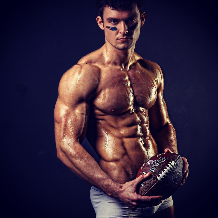 Josh Watson posing shirtless with a rugby ball, looking muscular and ripped