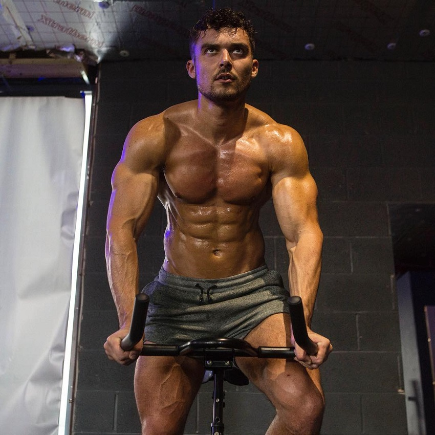Josh Watson doing cardio on a bike while shirtless