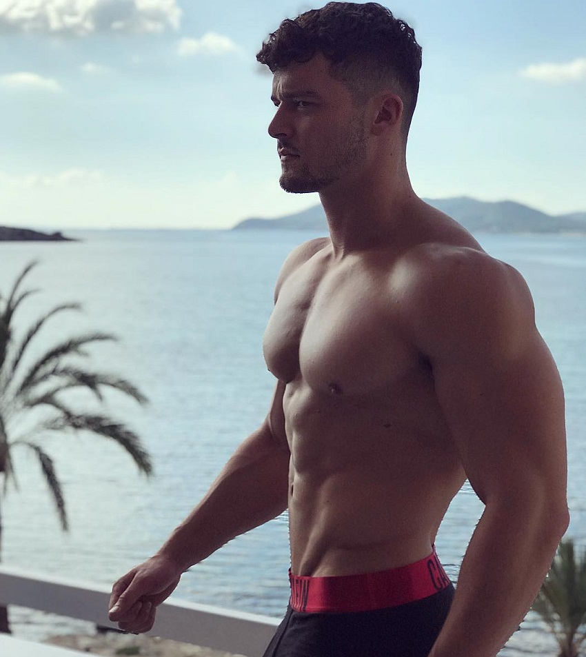 Josh Watson standing shirtless on the balcony overlooking a vast blue sea with islands