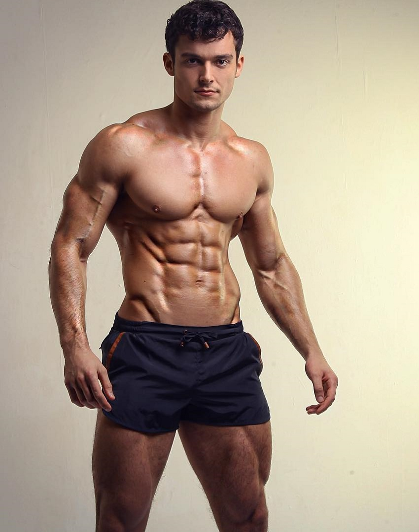 Josh Watson posing shirtless for a photo looking lean and strong