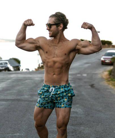 Matt Lucas flexing his biceps while wearing swimming shorts