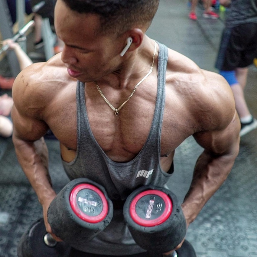 Mike Diamonds training with dumbbells in a gym looking ripped