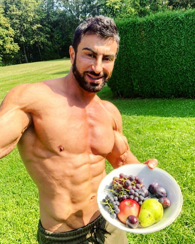 Murat Demir posing shirtless with a bowl of fruit