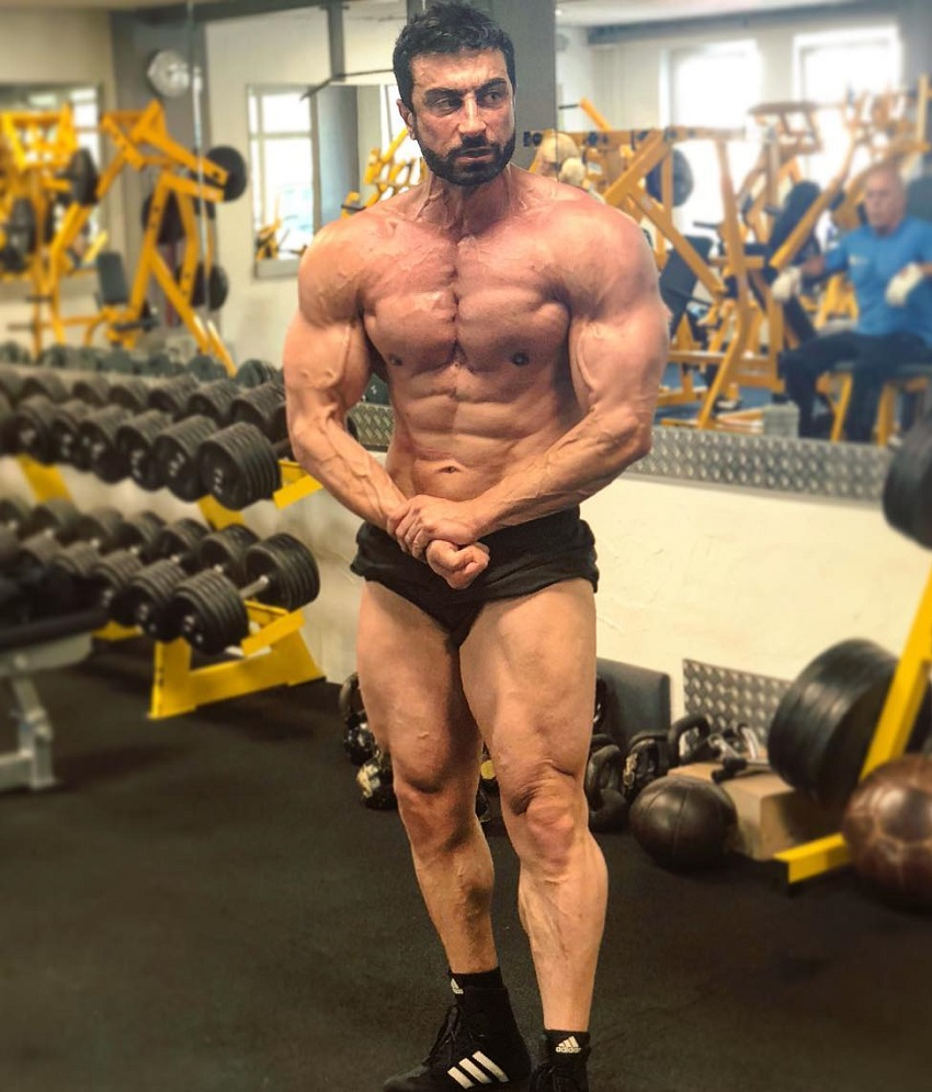 Murat Demir flexing his strong and ripped muscles in a gym