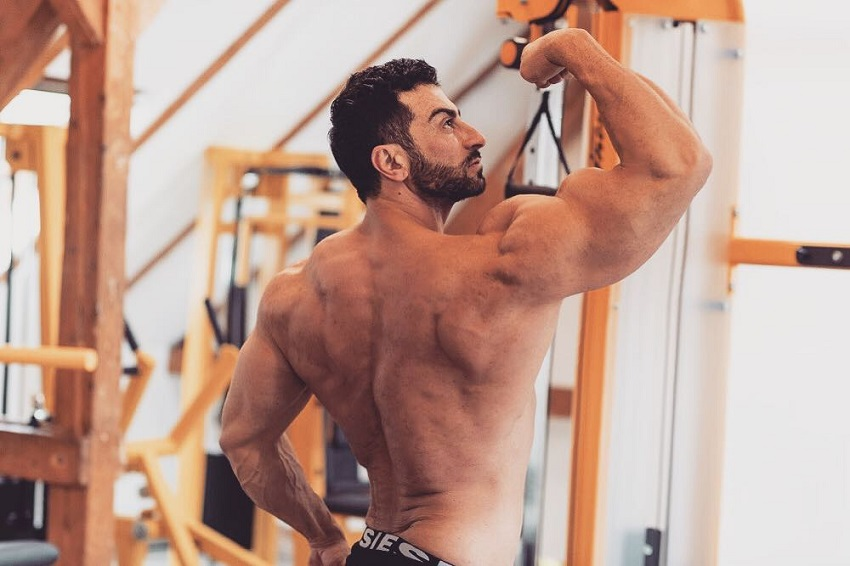 Murat Demir flexing his arms and back