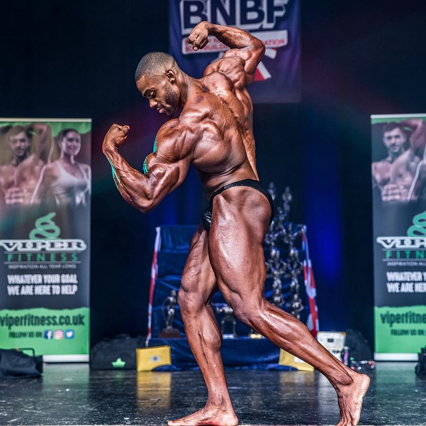Nathan Williams flexing his arms and back on the bodybuilding stage