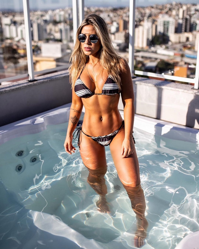 Sabrina Toledo posing in her bikini and sunglasses in a jacuzzi