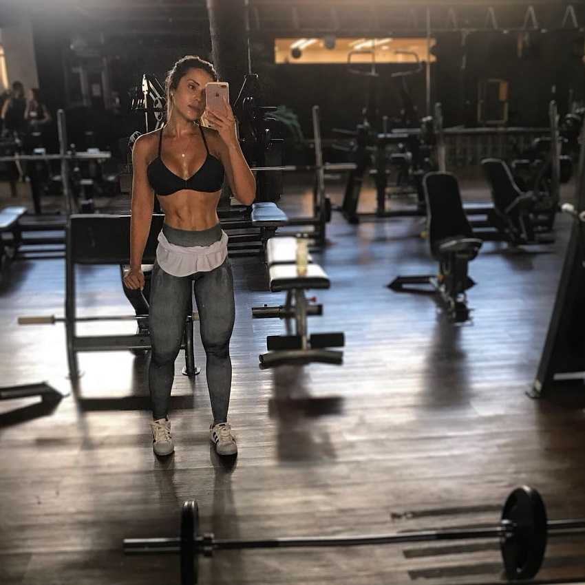 Sabrina Toledo taking a selfie of herself in a gym mirror looking fit and lean