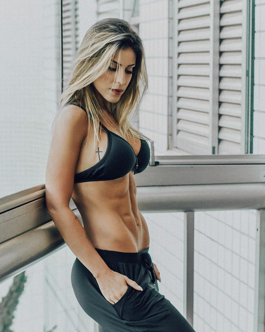 Sabrina Toledo leaning against a window displaying her lean and bulging abs