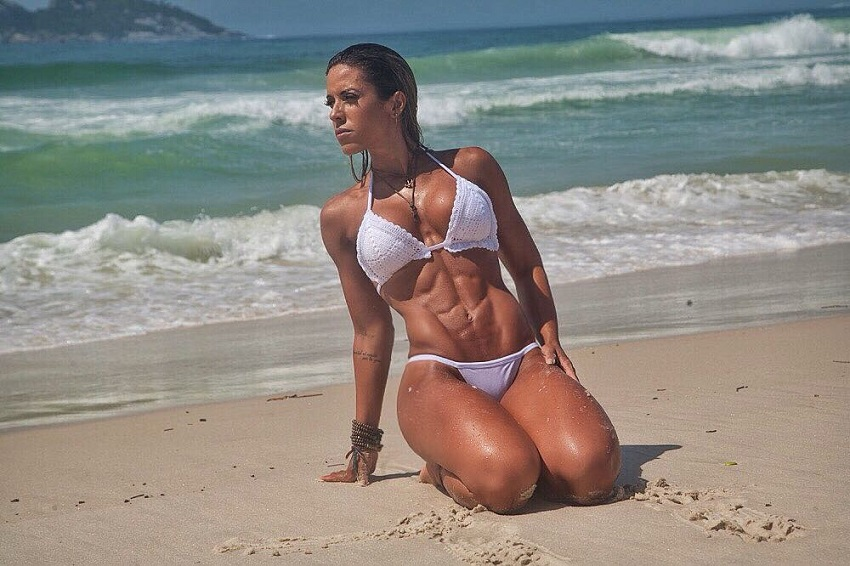Sabrina Toledo posing on a beach in her white bikini looking fit and curvy