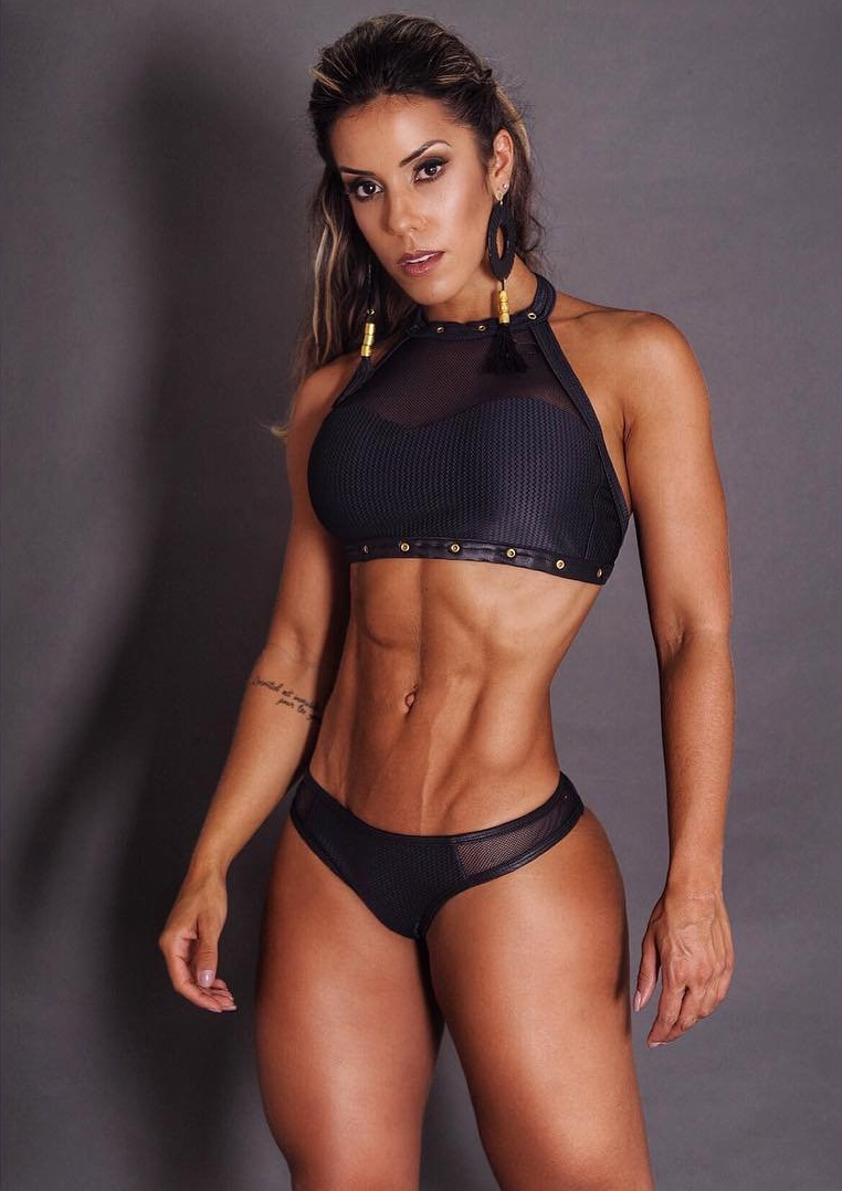 Sabrina Toledo posing for a photo with her ripped abs
