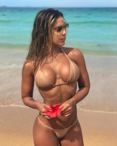 Sabrina Toledo standing on the beach in her swimsuit showing off her amazing body