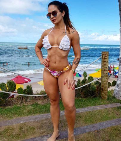 Sol Meneghini posing in a white bikini looking fit and lean