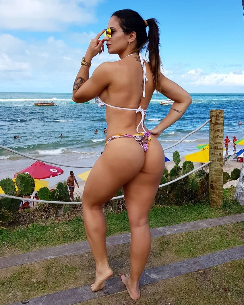 Sol Meneghini posing in a bikini near a beach, showing off her curvy glutes