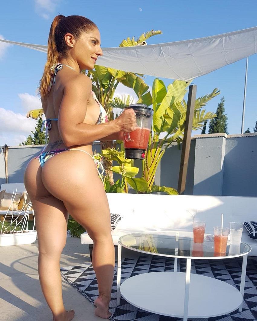 Sonia Amat Sánchez posing outdoors with a health smoothie in her hands looking curvy and fit