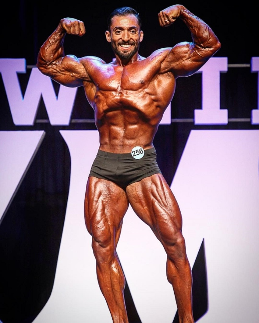 Abtin Shekarabi performing a front double biceps pose on the Joe Weider's Mr. Olympia stage 2018 Las Vegas